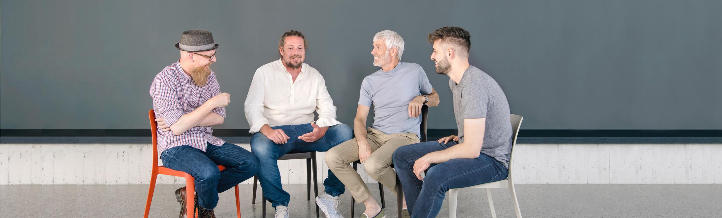 eine Gruppe von Männern sitzt an einem Tisch einem Stuhlkreis