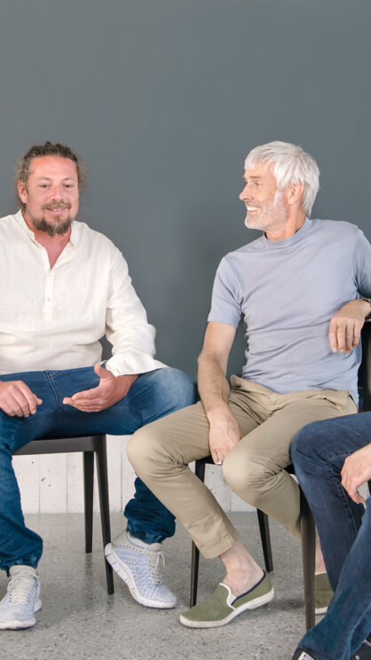 Vier Maenner sitzen in einer Runde und unterhalten sich