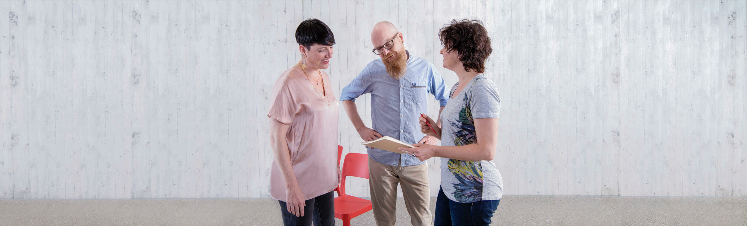 3 Personen stehen zusammen und unterhalten sich