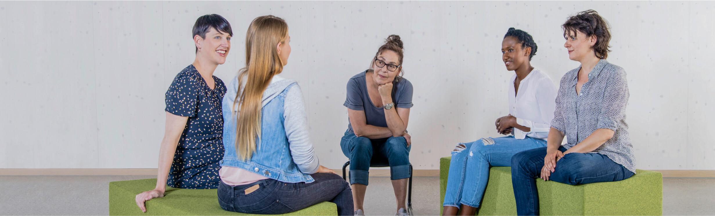 eine Gruppe von Frauen sitzt auf einem grünen Sofa und unterhält sich, alle hören einer jungen Dame zu